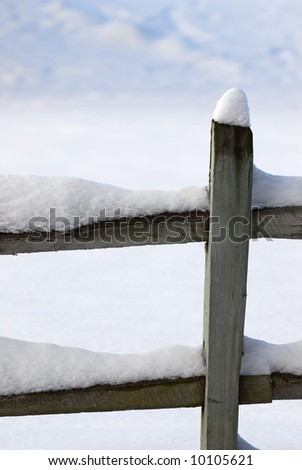Old fence covered with snow - stock photo