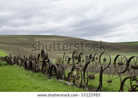 Old fence made of metal wheels.Rolling hill in background. - stock photo