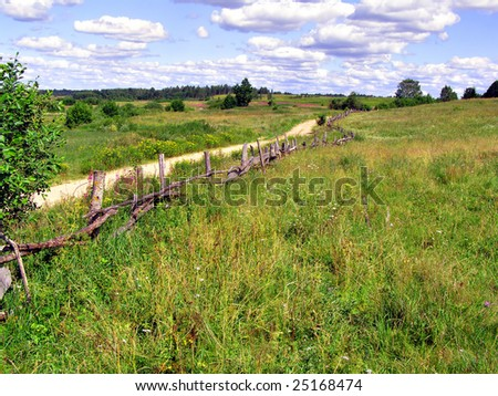 old fence near rural road - stock photo