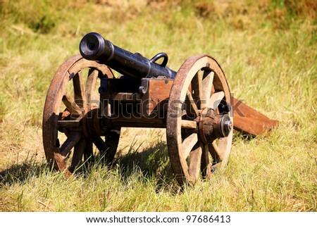 old field cannon shot on meadow grass - stock photo