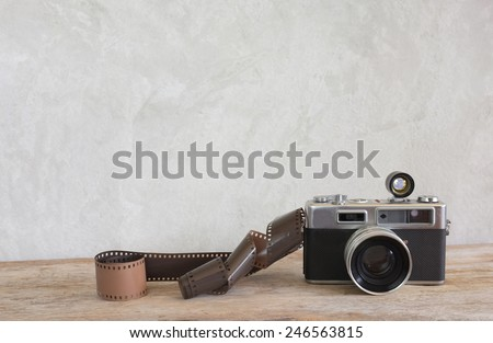 Old film camera and a roll of film on wood - stock photo