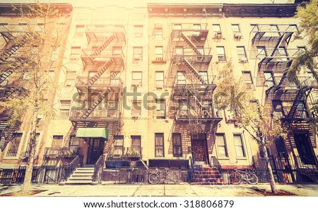Old film retro style photo of New York building with fire escape ladders, USA. - stock photo