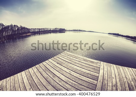 Old film retro toned fisheye lens image of a wooden pier a on lake at sunset. - stock photo