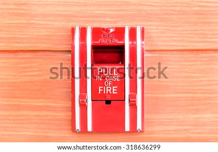 Old fire alarm on wood wall background - stock photo