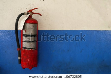 Old fire extinguisher tank on grunge blue wall - stock photo