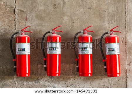 Old fire extinguishers attached on the grunge concrete wall - stock photo