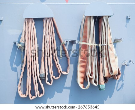 Old fire hose on blue wall - stock photo