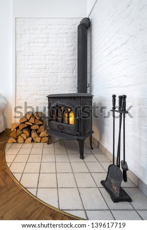 Old fireplace in modern interior design - stock photo