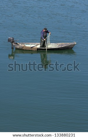 Old fisherman at estuary of Neretva river pulling net from water from his little boat - stock photo