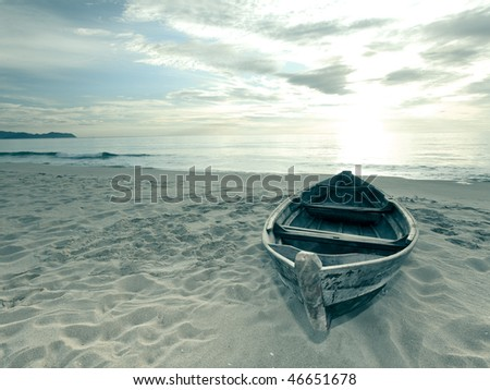 Old fisherman boat at sunrise time on the beach - stock photo