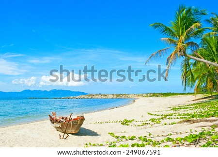 Old fisherman boat with anchor on the tropical palm beach - stock photo