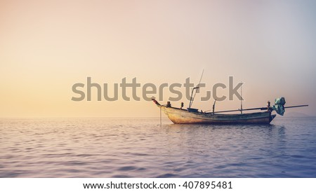 Old fisherman ship float on the sea, in sunrise - stock photo