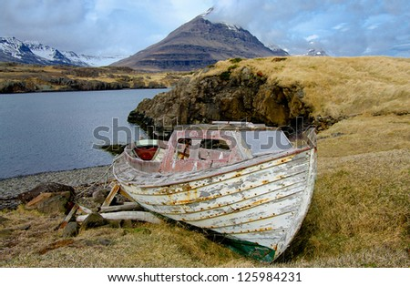 Old Fishing Boat:  A small, weathered boat rests on a remote shore in eastern Iceland. - stock photo
