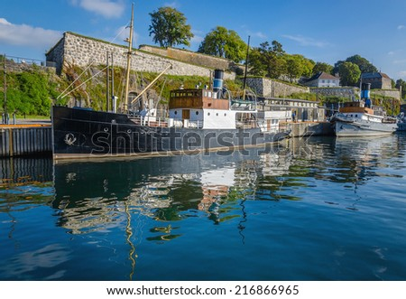 Old fishing boat and Akershus Fortress, Oslo, Norway  - stock photo