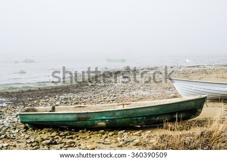 Old fishing boat at coast foggy in the morning - stock photo