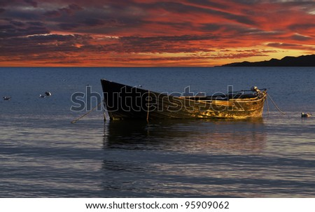 Old fishing boat at colorful sunset - stock photo