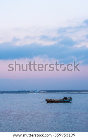 old fishing boat at sunset time against colorful sky
