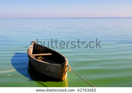 Old fishing boat floating on the water - stock photo
