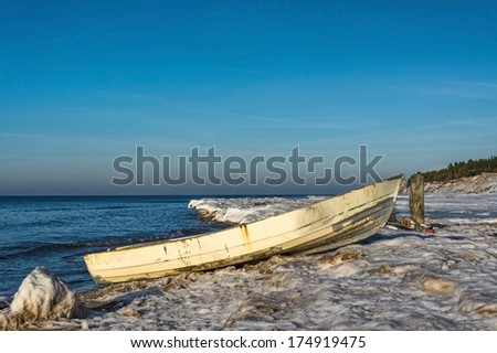 Old fishing boat in the wet snow, Baltic Sea, Latvia - stock photo