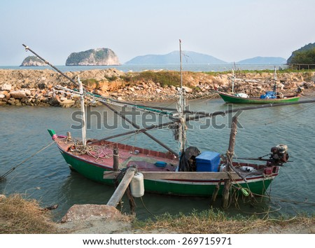 Old fishing boat is docked on the background of the shore rocks and grass  - stock photo