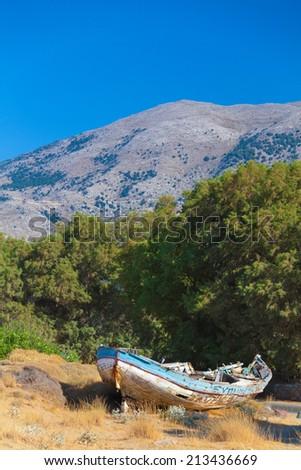 Old fishing boat left at Malia beach, Crete, Greece - stock photo