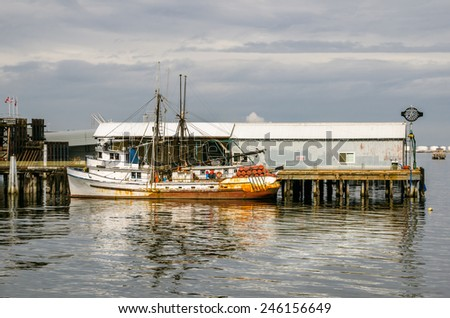 Old Fishing Boat Moored in a Harbour on a Cloudy Day - stock photo