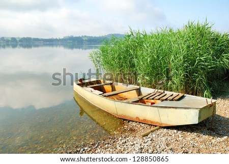 Old fishing boat on a lake shore - stock photo