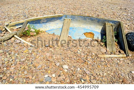 Old fishing boat on a pebble beach in Sidmouth, Devon - stock photo