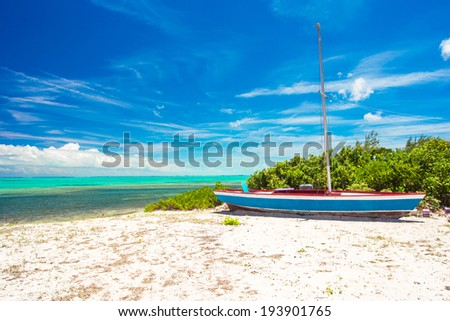 Old fishing boat on a tropical beach at the Caribbean - stock photo
