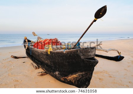 Old fishing boat on the sandy beach in Goa - stock photo