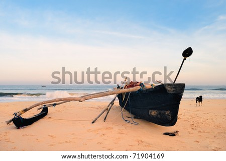 Old fishing boat on the sandy shore in Goa - stock photo