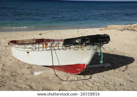Old fishing boat on tropical island beach with copy space - stock photo