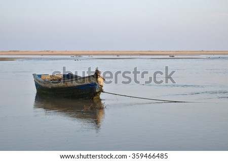 Old fishing boat resting on the low tide in Algarve, Portugal