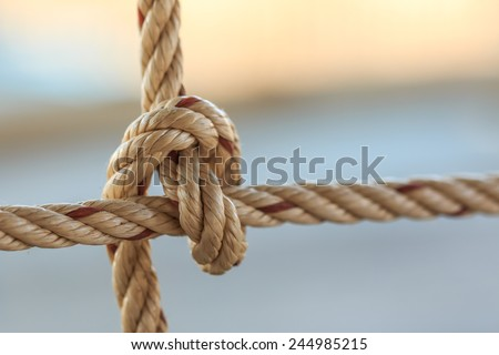 Old fishing boat rope with a Tied Knot - stock photo