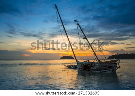 Old fishing boat stranded on a beach in sunny day - stock photo