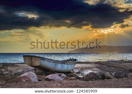 Old fishing boat thrown on the beach, Red Sea, Eilat, Israel - stock photo