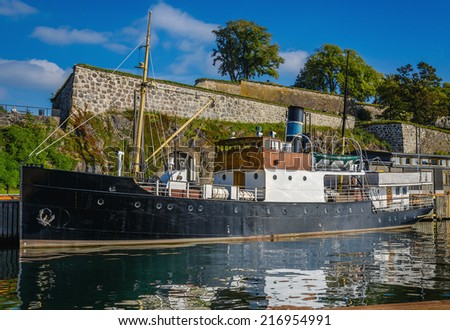 Old fishing boat under Akershus Fortress, Oslo, Norway  - stock photo