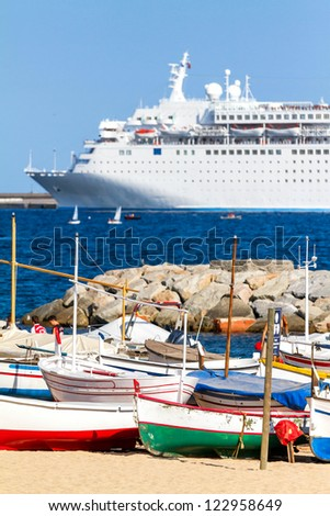 Old fishing boats and cruise ship - stock photo