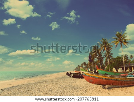 old fishing boats on beach in kerala india - vintage retro style - stock photo