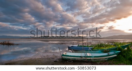 Old fishing boats on lake shore at dawn - stock photo