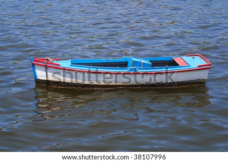 Old fishing boats with reflections in the sea - stock photo