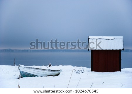 Old fishing cabin and rowboat in winter season by the coast of the swedish island Oland in the Baltic Sea