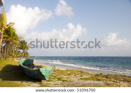 old fishing kayak boat by caribbean sea on desolate undeveloped sallie peachie beach corn island nicaragua central america - stock photo