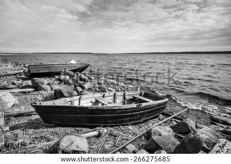 Old fishing motor boat on lake coast in Karelia. Black and white photo - stock photo