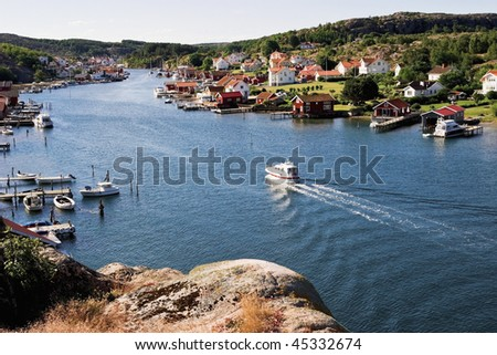 Old fishing village at the coast and a motorboat in the canal - stock photo