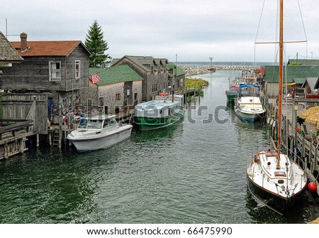 old fishing village with boats anchored in channel
