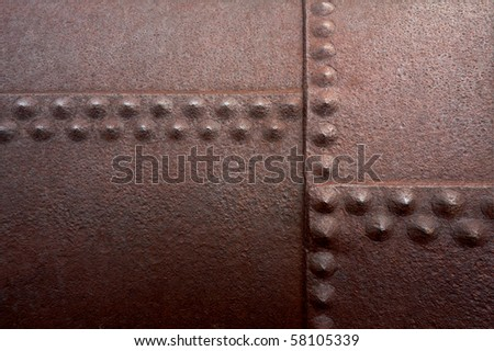 Old flat metal with pitting, rust and rivets.