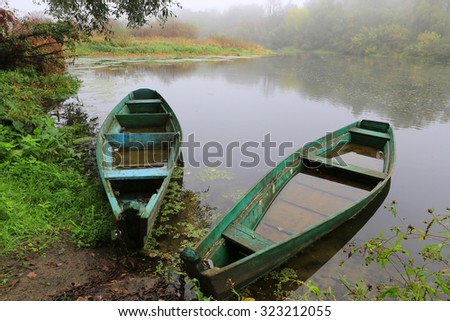 old flooded wooden boats on river - stock photo