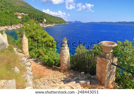 Old flower pots along rocky trail above the shore of the Adriatic sea, Trsteno, Croatia - stock photo