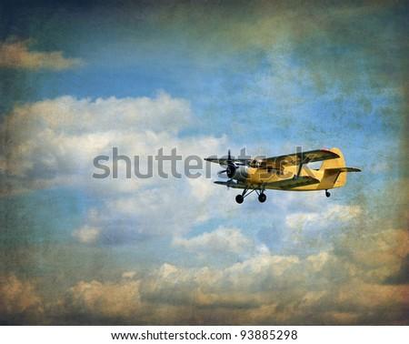 Old flying biplane, retro aviation background - stock photo